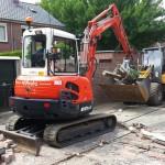 Minigraver en loader om puin weg te rijden